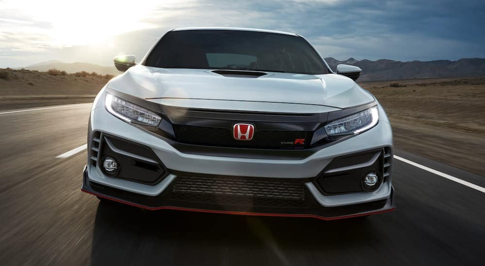 A white 2021 Honda Civic Type-R is driving on a highway, shown from the front.