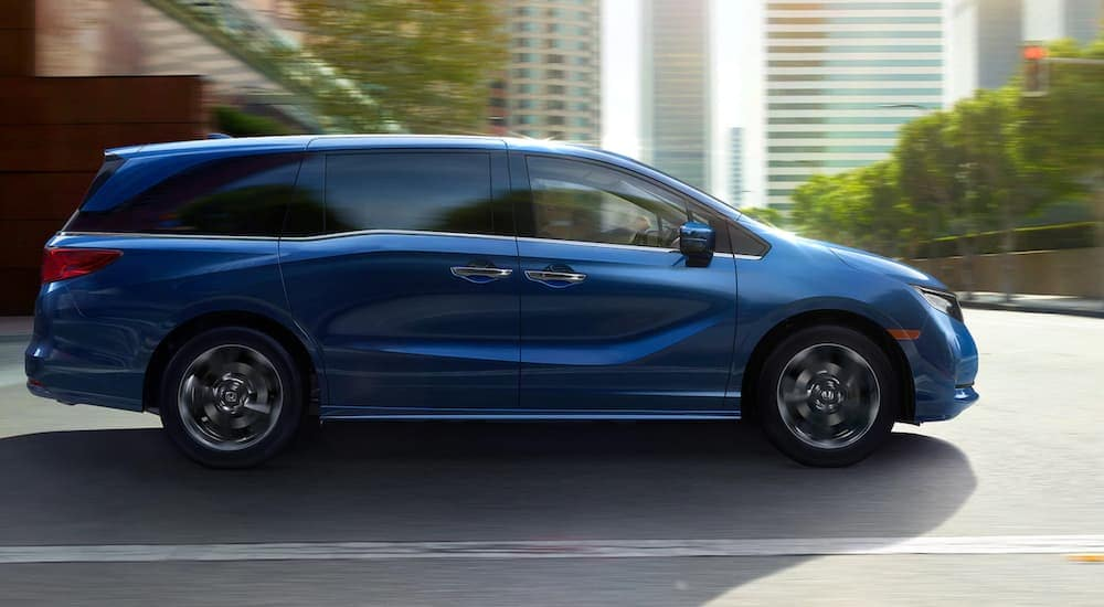 A blue 2021 Honda Odyssey Elite is shown from the side on a city street near Duluth, GA.