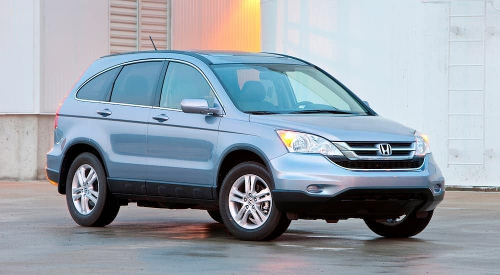 A light blue 2011 used Honda CR-V is parked in front of a white building near Duluth, GA.
