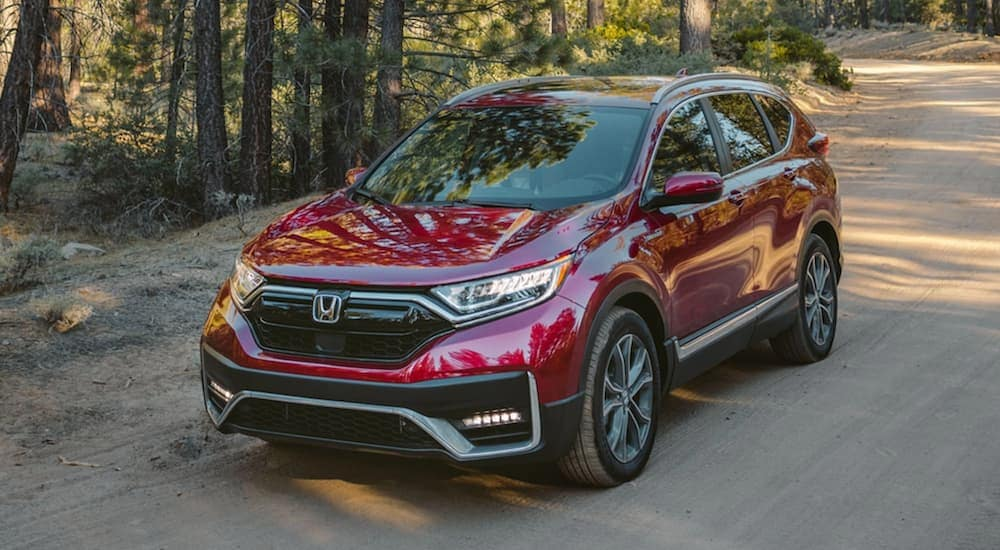A dark red 2020 Honda CR-V Hybrid Touring is driving on a dirt road.