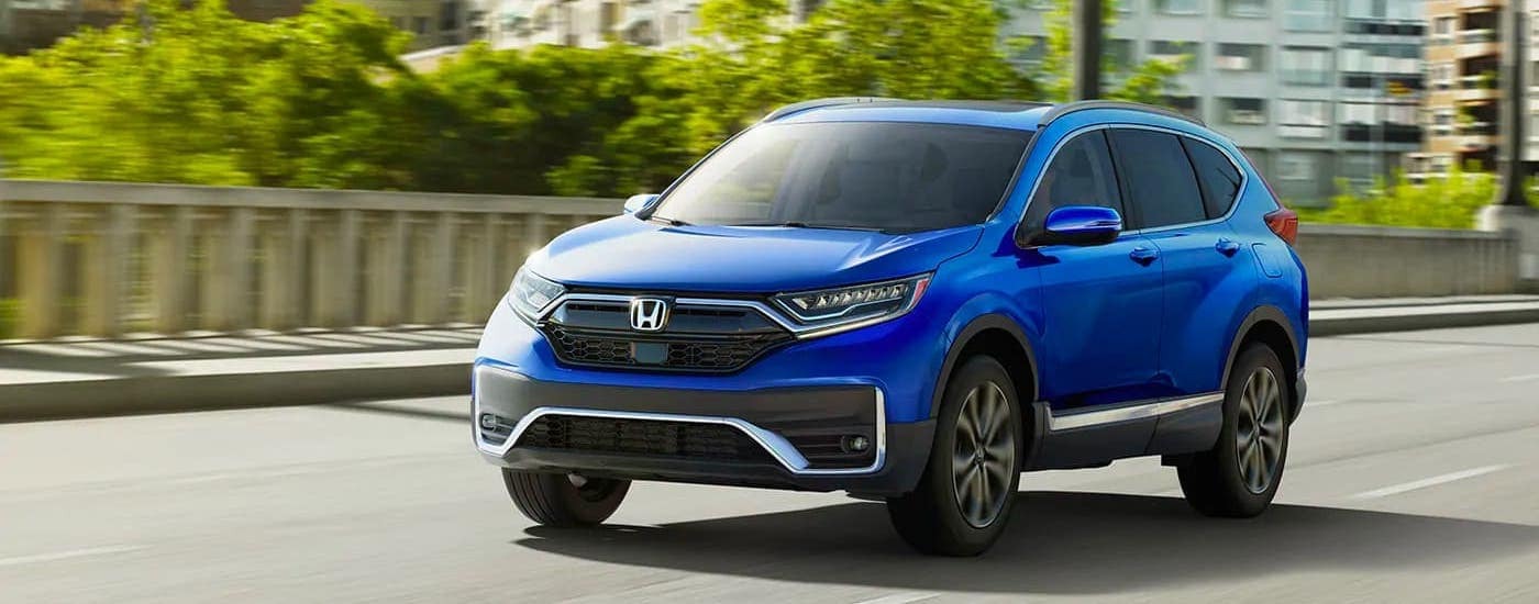A blue 2020 Honda CR-V Touring is driving on a city street.