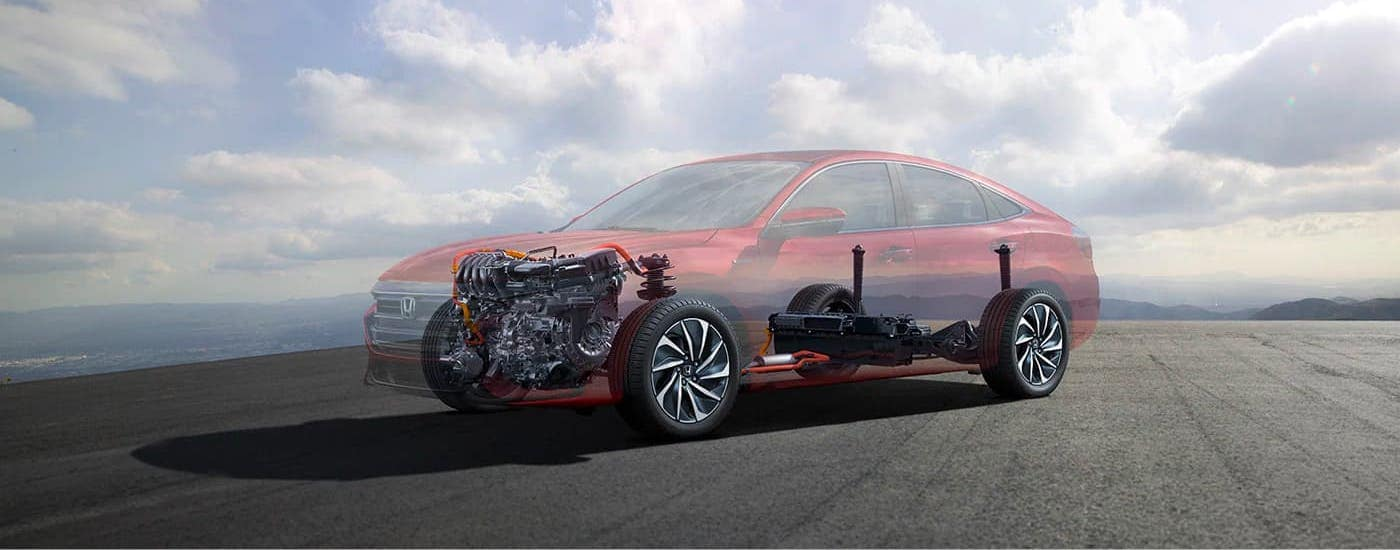 A simulated cross sections hows the hybrid engines in a red 2021 Honda Insight Touring against a cloudy sky.