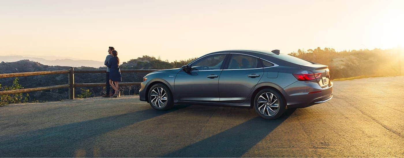 A couple is standing outside a gray 2021 Honda Insight and overlooking a canyon at sunset.