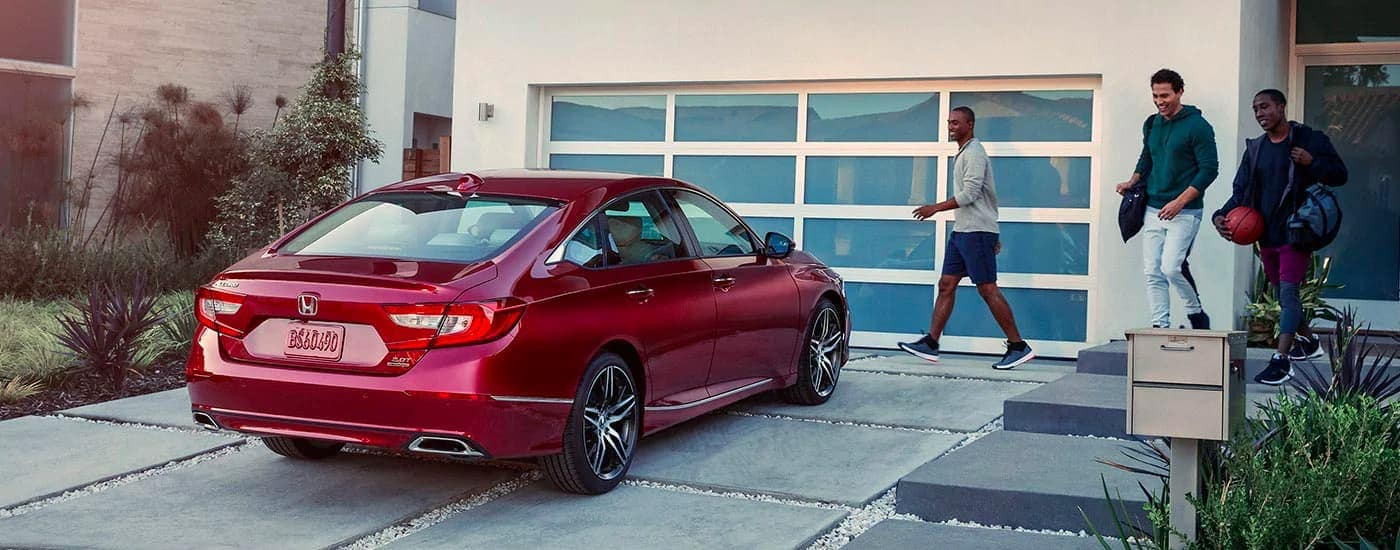 Three young men are walking towards a red 2020 Honda Accord Touring 2.0T with basketball gear.