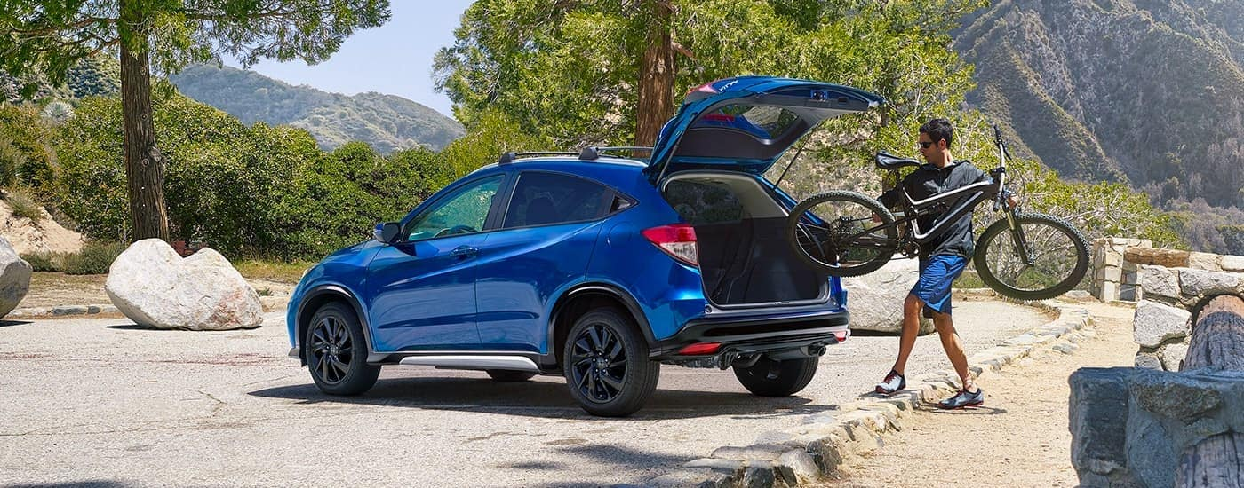 A man is loading a bike into the rear of a blue 2020 Honda HR-V Sport.