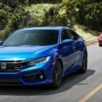A blue and a red 2016 used Honda Civic Sedan SI are driving down a wooded raod.