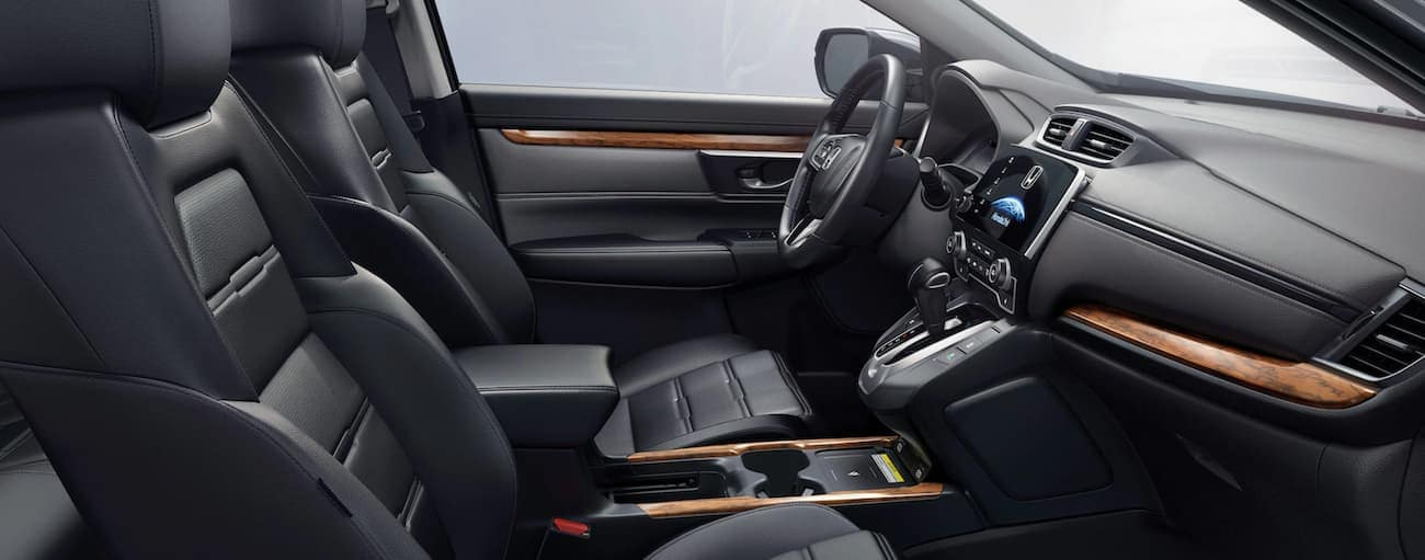 The black interior of a 2021 Honda CR-V Touring is shown from the side.