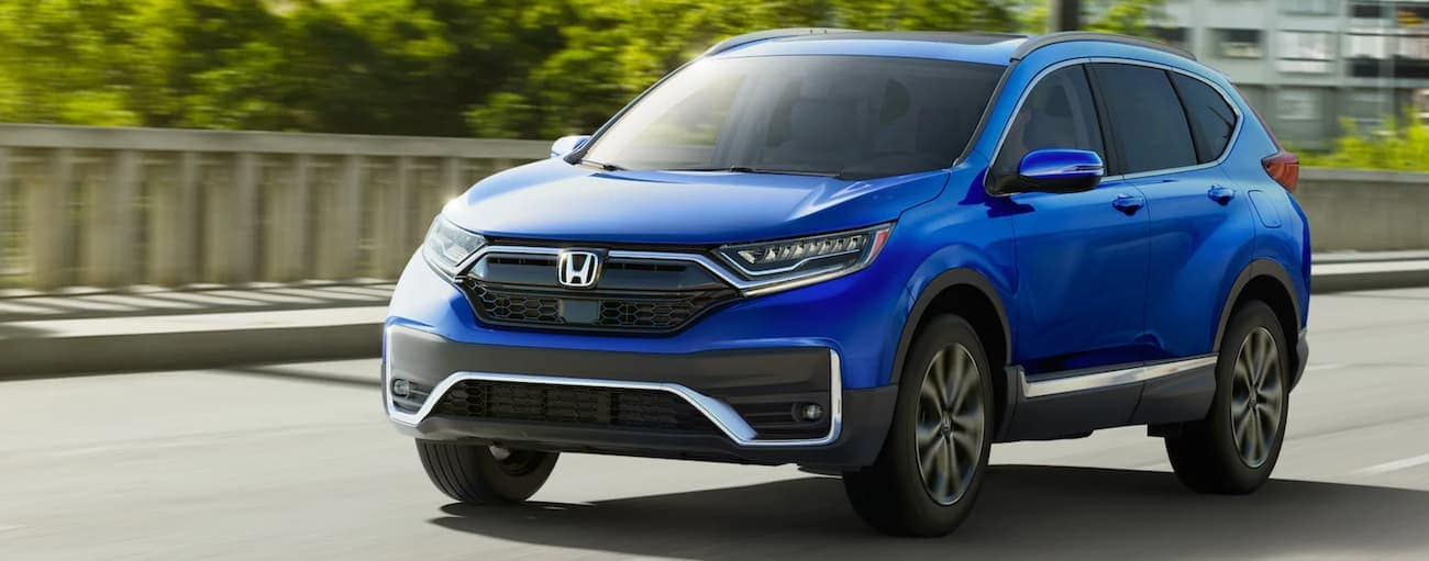 A blue 2021 Honda CR-V Touring is driving on a road past trees after winning the 2021 Honda CR-V vs 2021 Toyota RAV4 comparison.