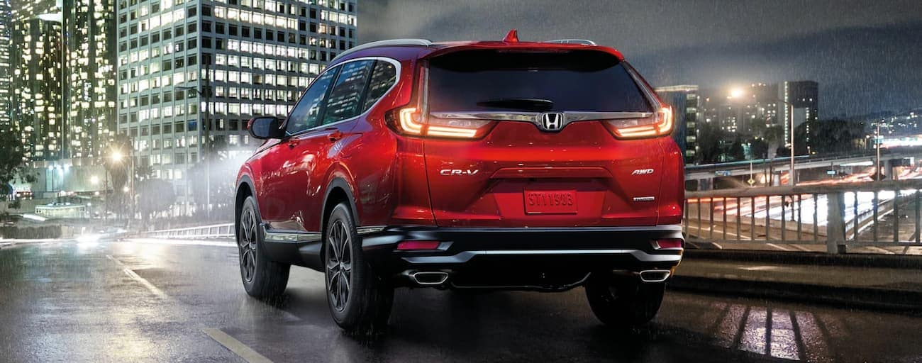 A red 2021 Honda CR-V Touring is driving on a wet street into a city in the rain.