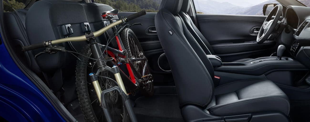 The black interior of a 2021 Honda HR-V EX-L is shown from the side with a bike in the folded rear seat.