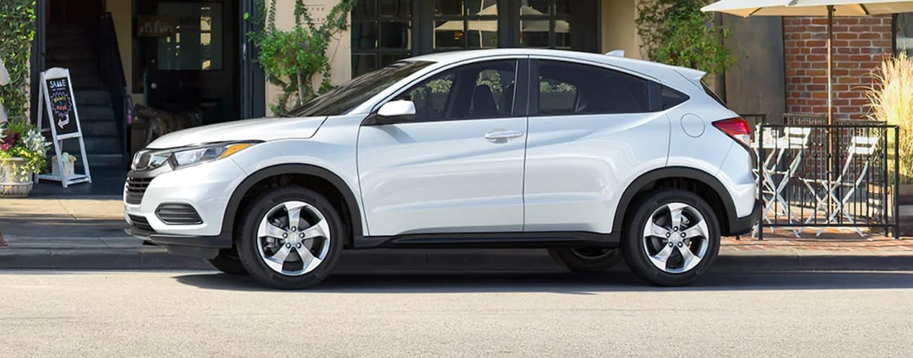 A white 2021 Honda HR-V LX is parked on a city street.