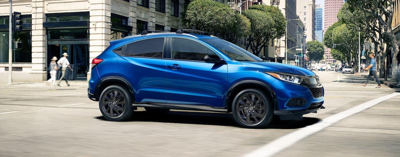 A blue 2021 Honda HR-V Sport is driving through a city intersection.
