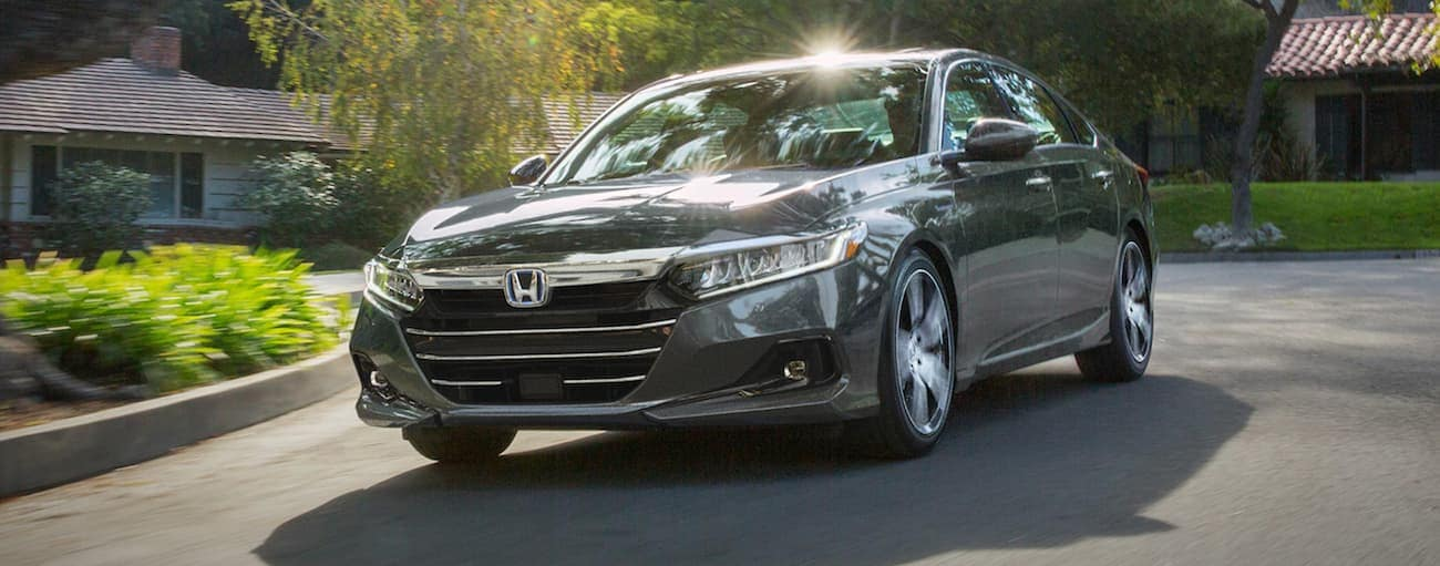 A grey 2021 Honda Accord Hybrid Touring is driving through a neighborhood on a sunny day.