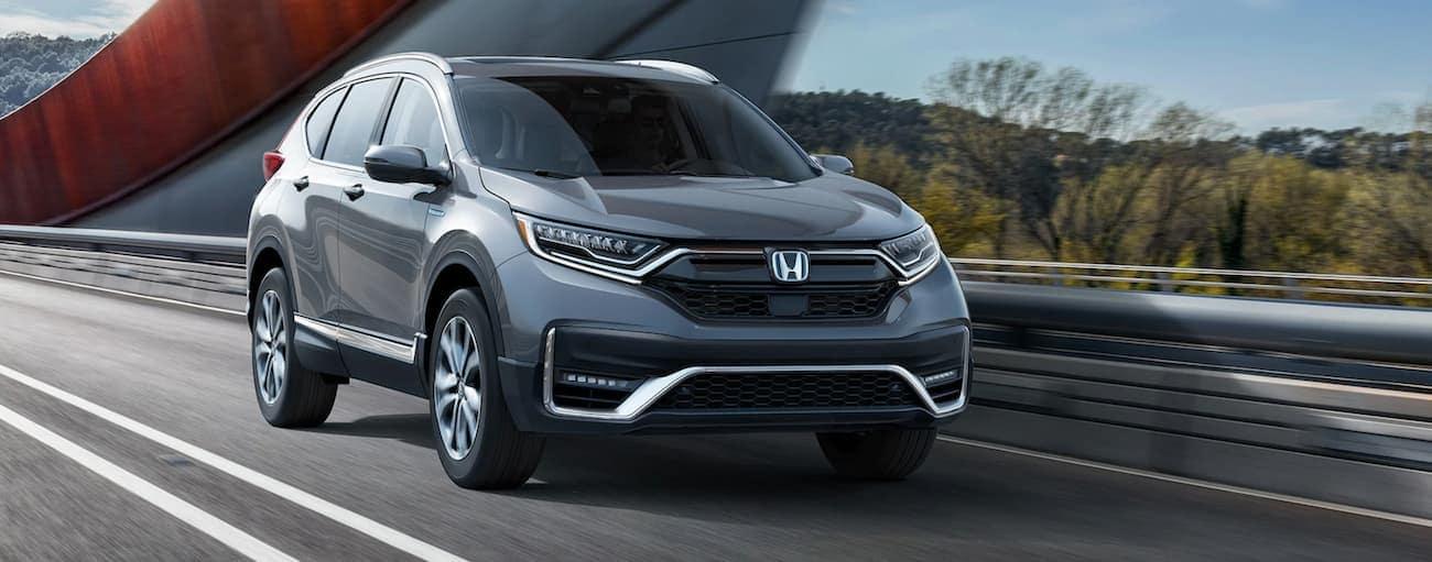 A popular 2021 Honda Hybrid, a grey CR-V Hybrid Touring is driving over a bridge.