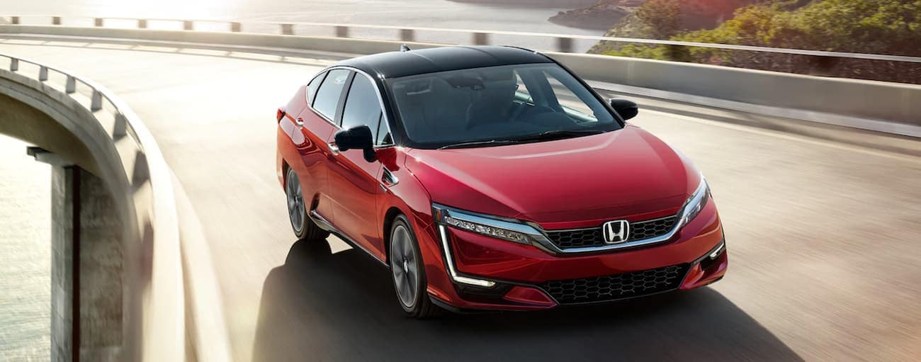 A red 2021 Honda Clarity Fuel Cell is driving on a highway over a body of water.