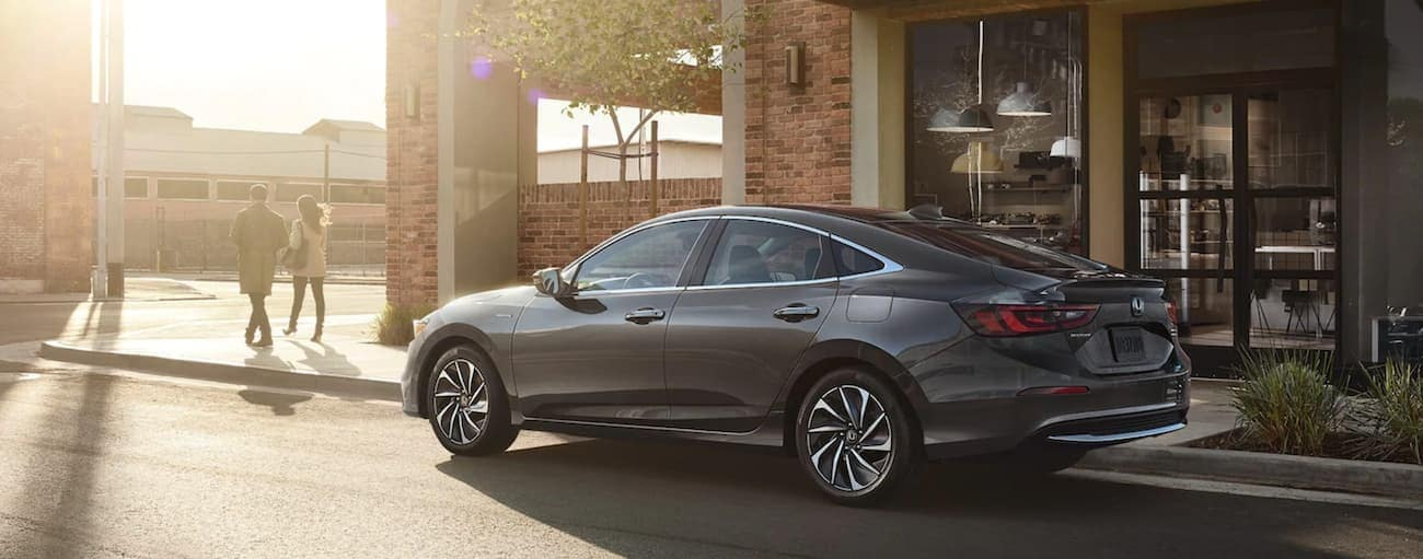 A couple is walking away from a 2021 Honda Insight on a sunny city street.