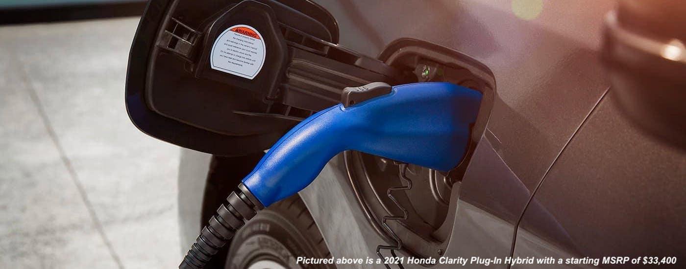 A closeup shows the blue plug attached to a gray 2021 Honda Clarity Plug-in Hybrid, a newer 2021 Honda hybrid.