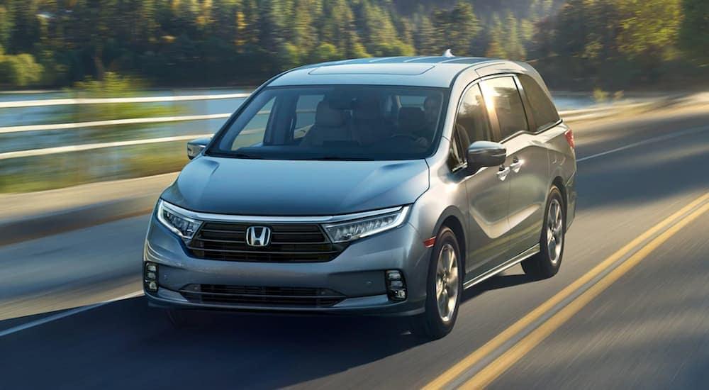 A grey 2021 Honda Odyssey Elite is driving past a lake after leaving a Honda dealership in Atlanta.
