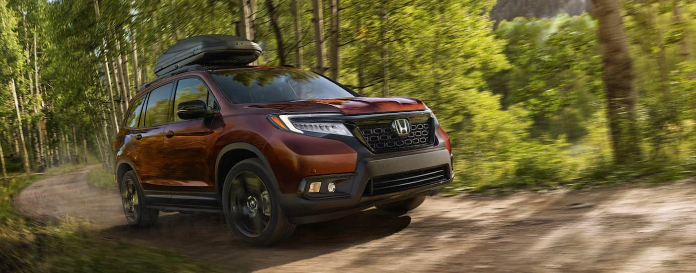 A burgundy 2021 Honda Passport Elite is driving on a dirt road in the woods.