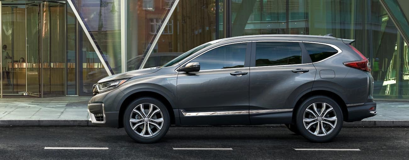 A grey 2021 Honda CR-V Touring Hybrid is shown from the side in front of a glass building.