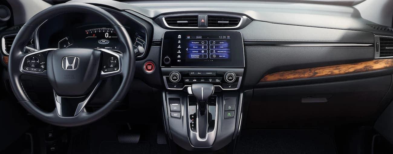 The dashboard and infotainment screen are shown in a 2021 Honda CR-V Touring.