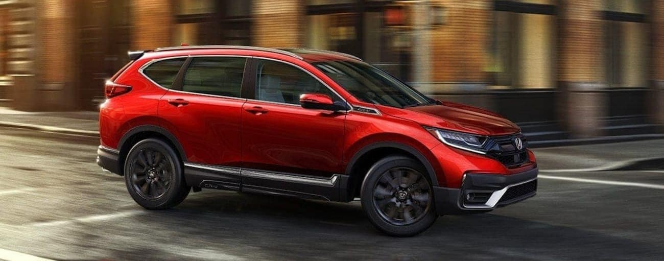 A red 2021 Honda CR-V Touring is driving on a city street after winning the 2021 Honda CR-V vs 2021 Nissan Rogue comparison.