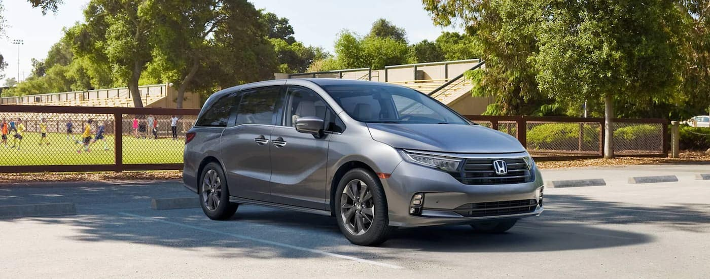 A silver 2022 Honda Odyssey Elite is shown parked in front of a soccer field.