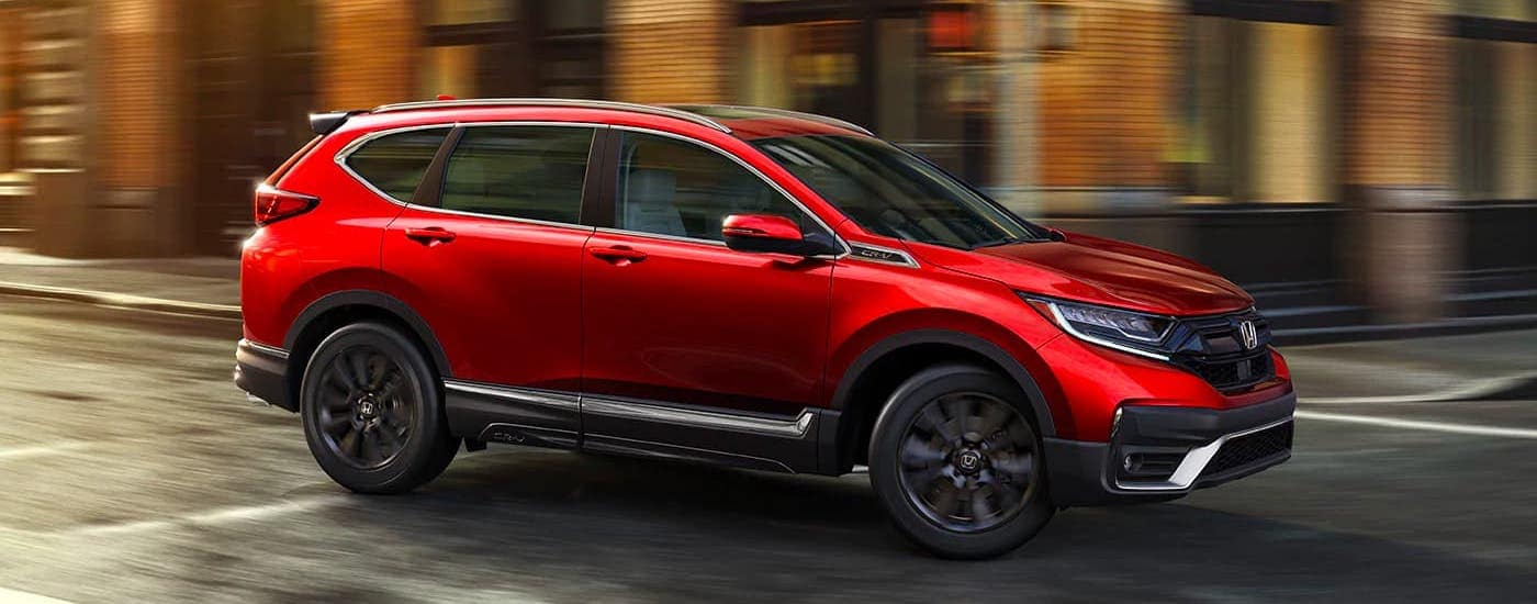 A red 2021 Honda CR-V Touring is driving on a city street.