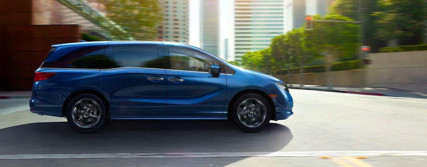 A blue 2021 Honda Odyssey is shown from the side driving on a city street after leaving a Honda dealership in Atlanta.