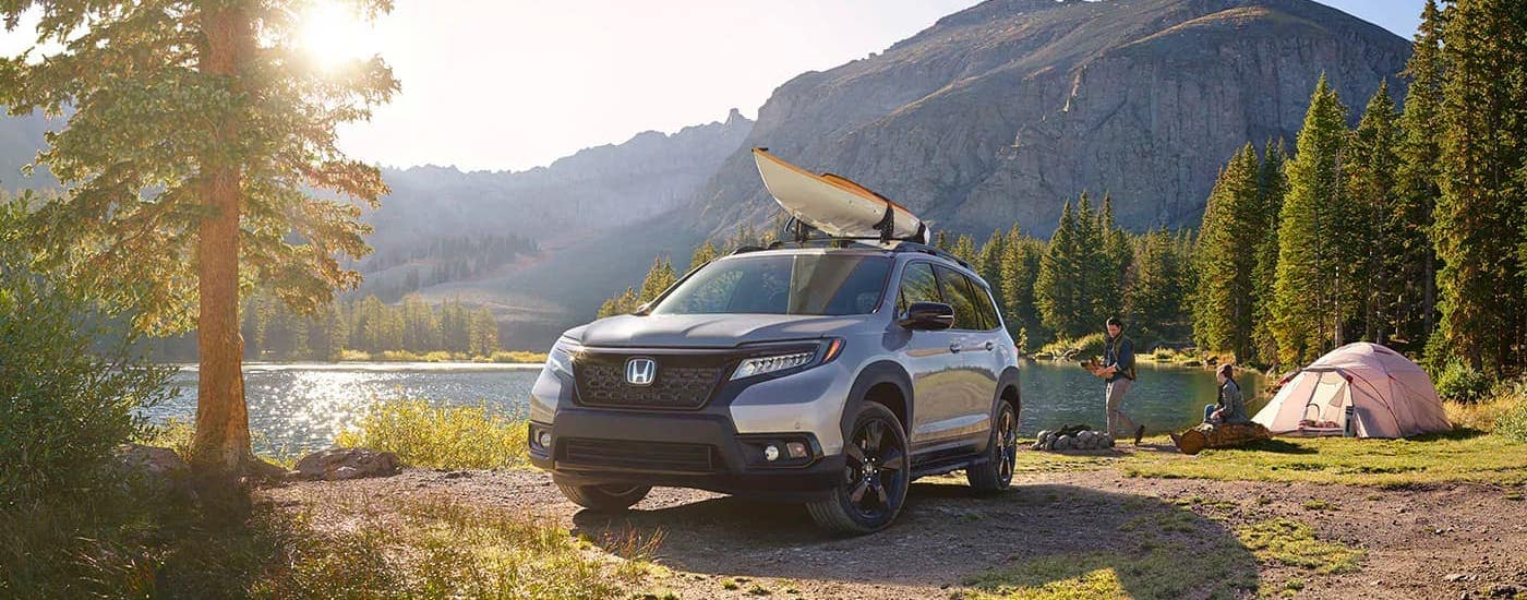 A silver 2021 Honda Passport Elite with a canoe on the roof is parked in front of a pond and campsite.