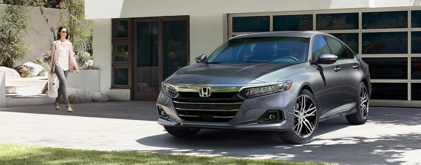 A woman is walking toward a grey 2021 Honda Accord Touring in front of a white modern house.