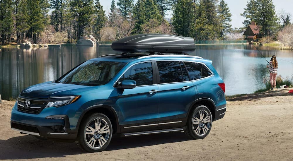 A blue 2020 used Honda Pilot is parked by a lake near a woman fishing.