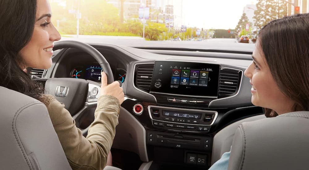 A mother and daughter are shown in the front seats of a 2020 used Honda Pilot.