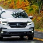 A white 2020 used Honda Pilot is shown from the front driving down a twisty road.