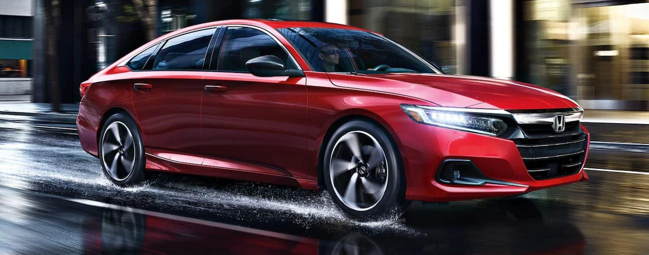 A red 2021 Honda Accord Sport is driving on a wet city street.