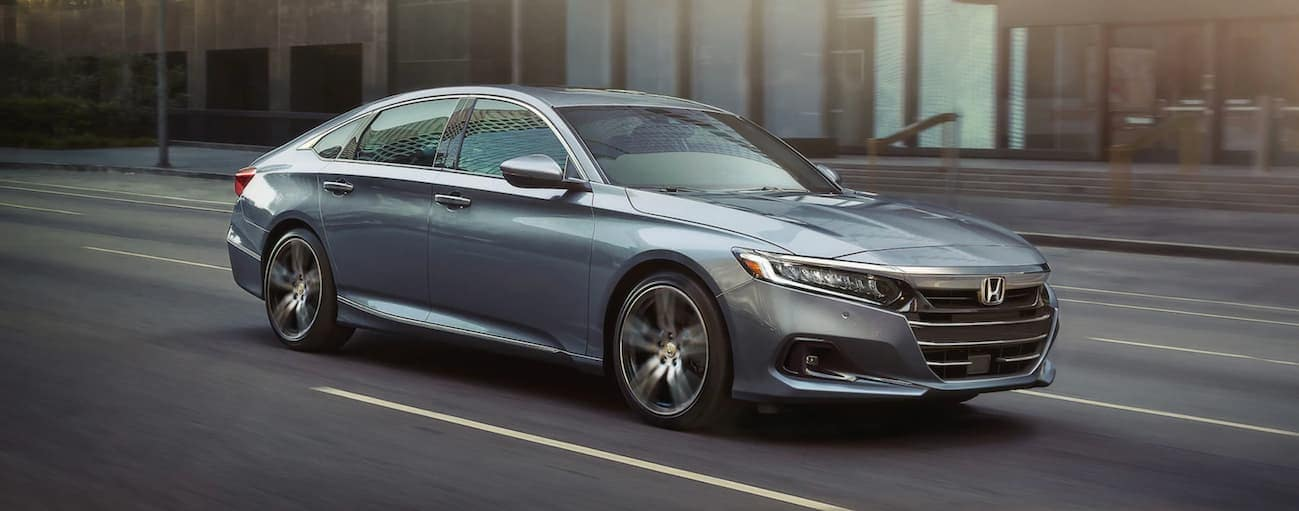 A grey 2021 Honda Accord Touring is driving on a city street after winning the 2021 Honda Accord vs 2021 Toyota Camry comparison.
