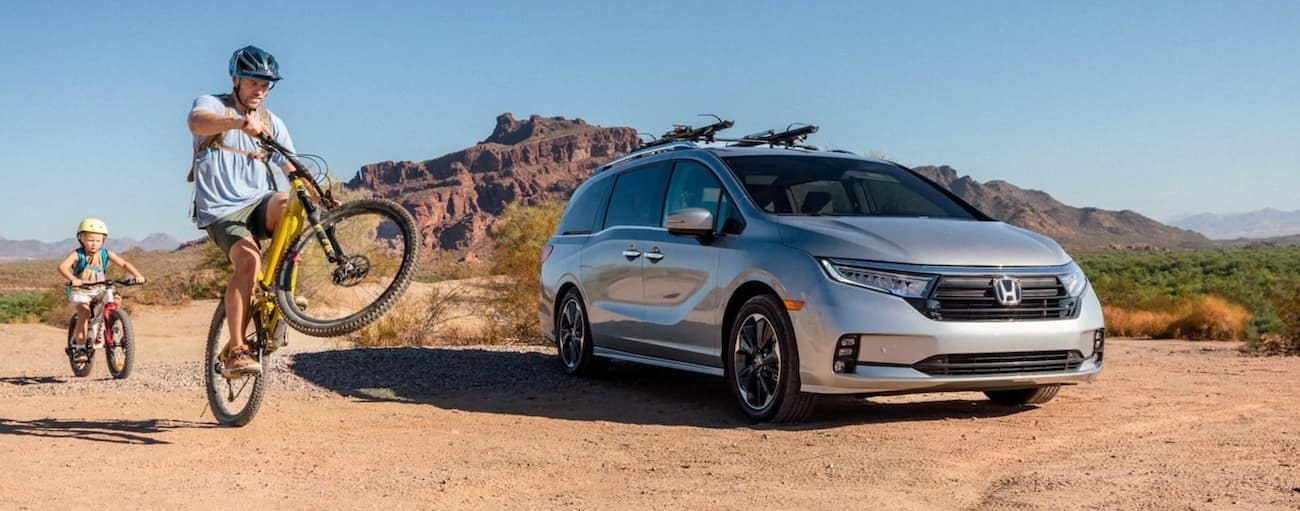 A dad and child are riding bikes next to a silver 2022 Honda Odyssey Elite parked in the desert.