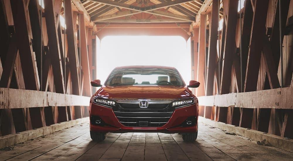 A red 2021 Honda Accord is shown driving through a covered bridge after leaving an Atlanta Honda Accord dealer.