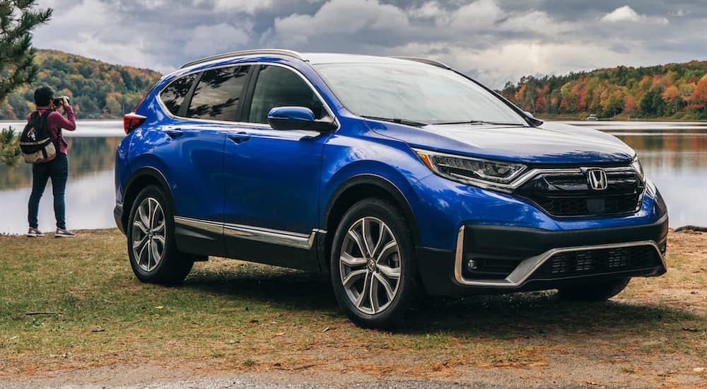 A blue 2021 Honda CR-V from a Honda dealership in Atlanta is parked in front of a lake with a woman taking pictures.