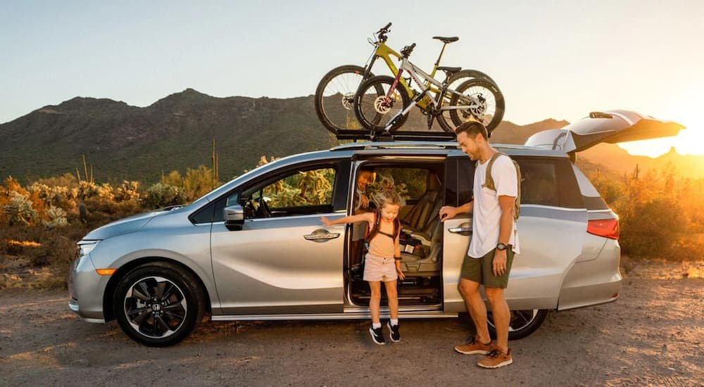 A father is opening the rear door for his daughter in a silver 2021 Honda Odyssey Elite with bikes on the roof.