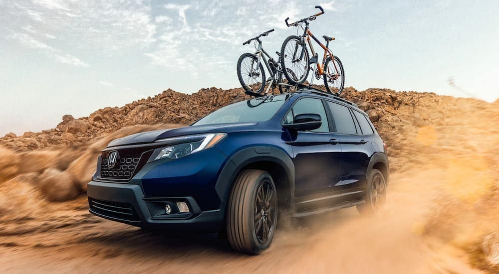 A blue 2021 Honda Passport Sport is driving on a dirt road in the desert with bikes on the roof.
