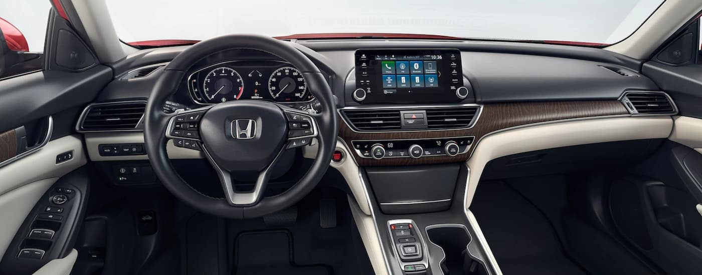 The tan and black front seats and dash are shown in a 2021 Honda Accord.