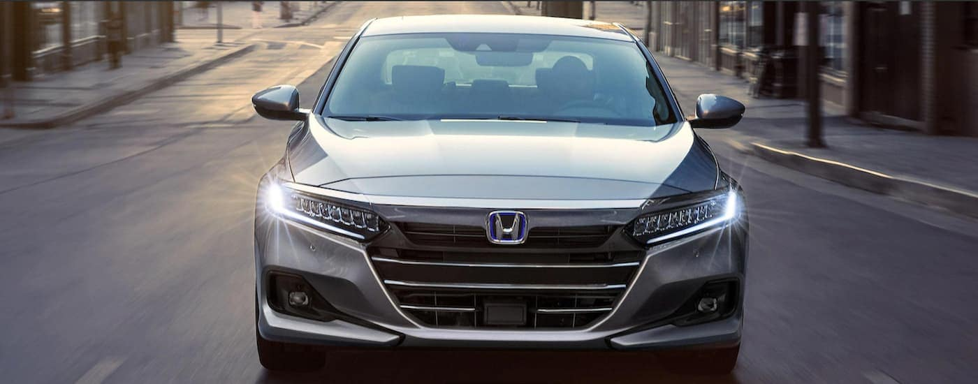 A gray 2021 Honda Accord hybrid is shown from the front driving through the city.