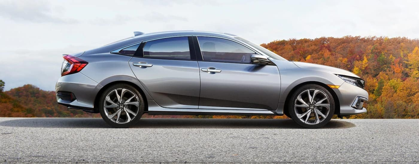A silver 2021 Honda Civic is shown from the side parked in an empty lot with hills in the background.