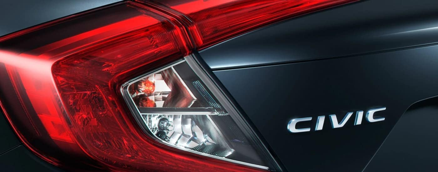 A close up shows the tail lights and Civic emblem on a dark grey 2021 Honda Civic.