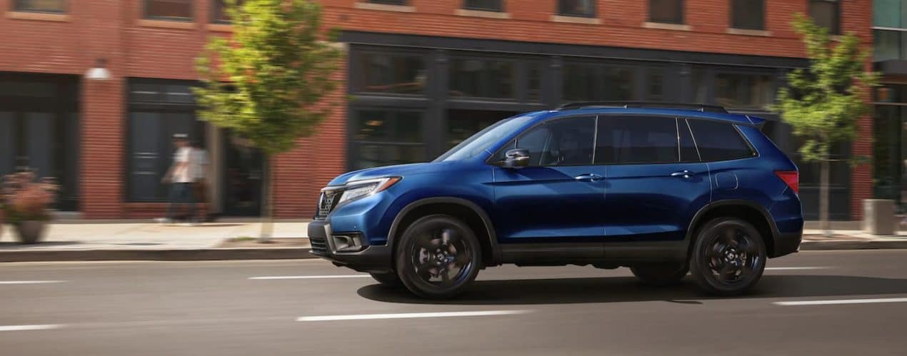 A blue 2021 Honda Passport Elite is shown from the side driving down a city street.