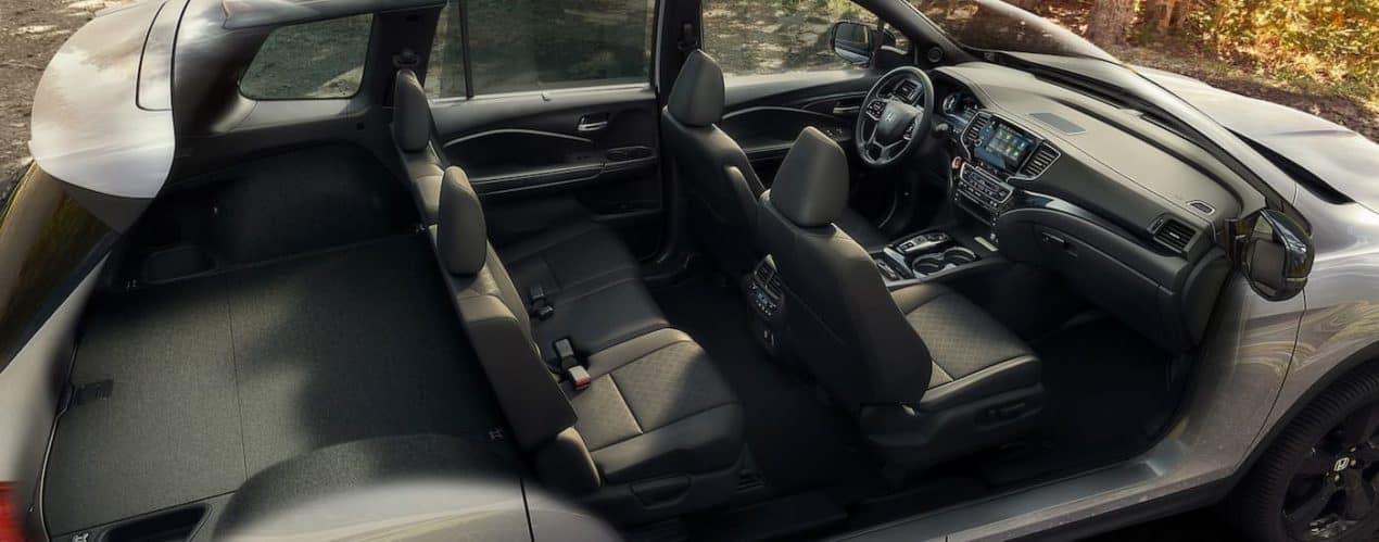 A cutaway shows the full black interior of a silver 2021 Honda Passport Elite.