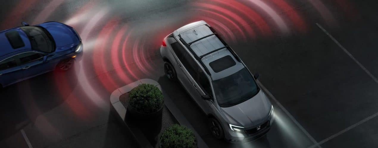 A silver 2021 Honda Passport Elite is shown from a high angle with simulated blind spot monitoring sensor lines.