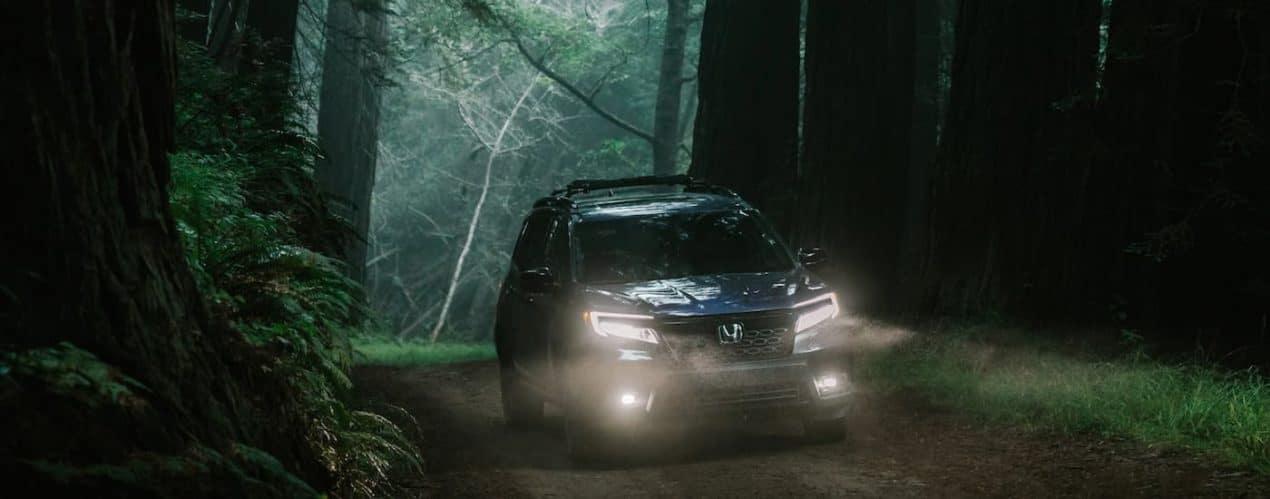 A dark blue 2021 Honda Passport Elite is shown from the front driving through a dark forest.
