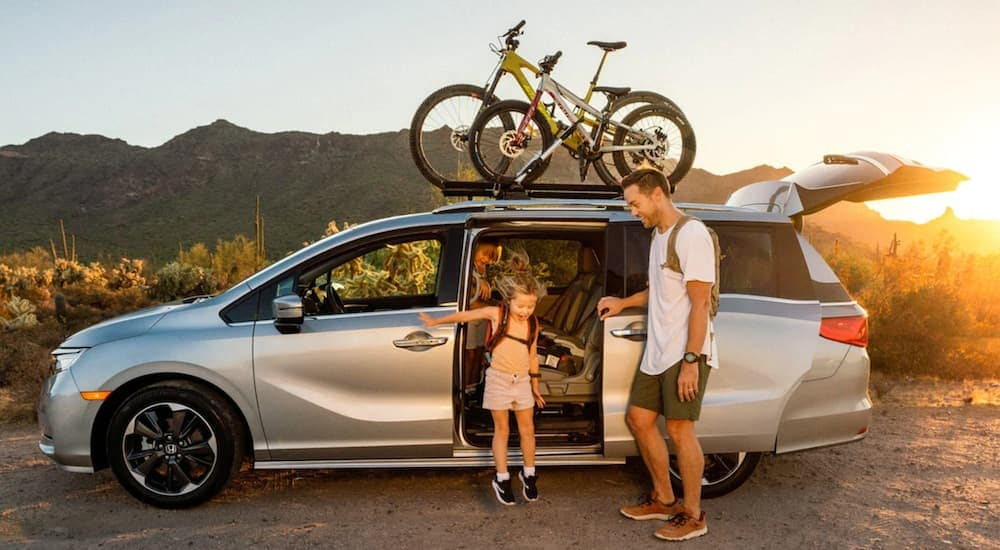 A silver 2019 used Honda Odyssey is shown from the side with bikes on the roof and a little girl hopping out of the sliding door.